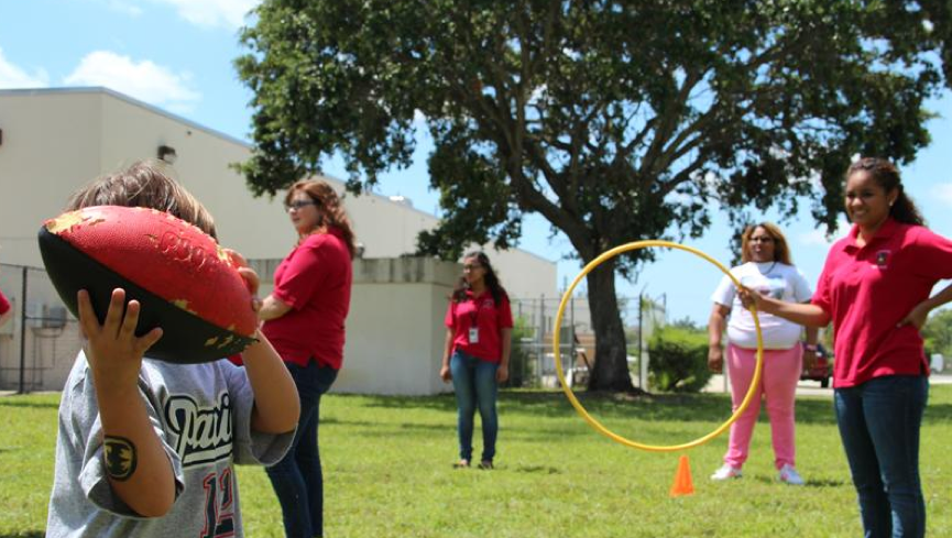 Early Childhood student Leishaly Diaz holds the hoop for the hoop toss game.