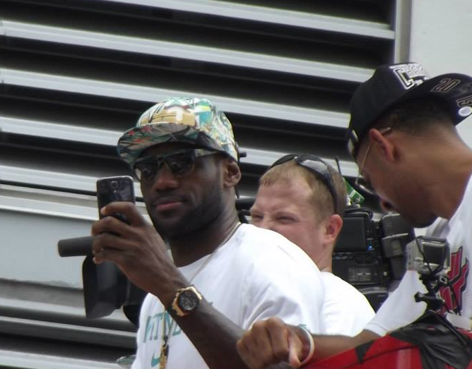 Lebron James takes pictures and video of the fans.