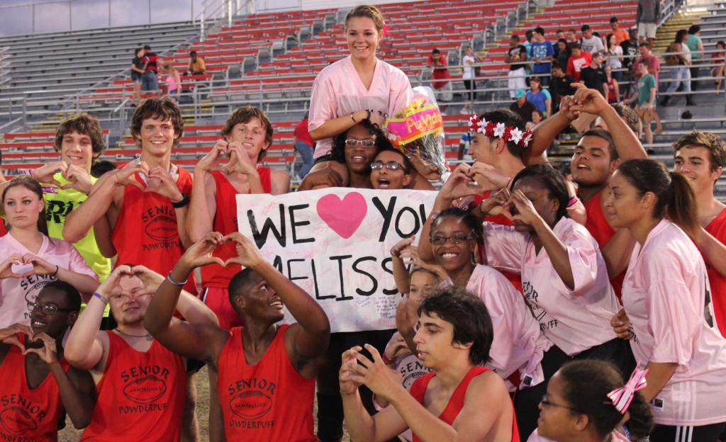 At+the+Powder+Puff+Football+game%2C+they+raise+Melissa+to+support+her+after+losing+her+mother+to+breast+cancer.