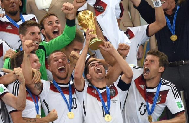 Philipp Lahm, center, of Germany lifts up the World Cup trophy between his teammates Lukas Podolski, second from left, and Thomas Mueller, right, and Mario Goetze, top, after winning the FIFA World Cup 2014 final soccer match between Germany and Argentina at the Estadio do Maracana in Rio De Janeiro, Brazil, Sunday, July 13, 2014. Germany defeated Argentina 1:0. (Marcus Brandt/DPA/Zuma Press/MCT)
