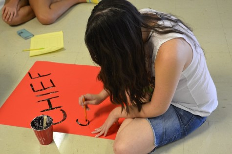 Nicole McGarity paints the Chiefs Squad sign.