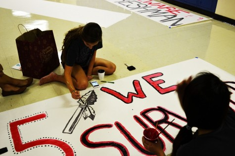 "Victoria Hanley paints the ""1-5 We Survived"" banner."