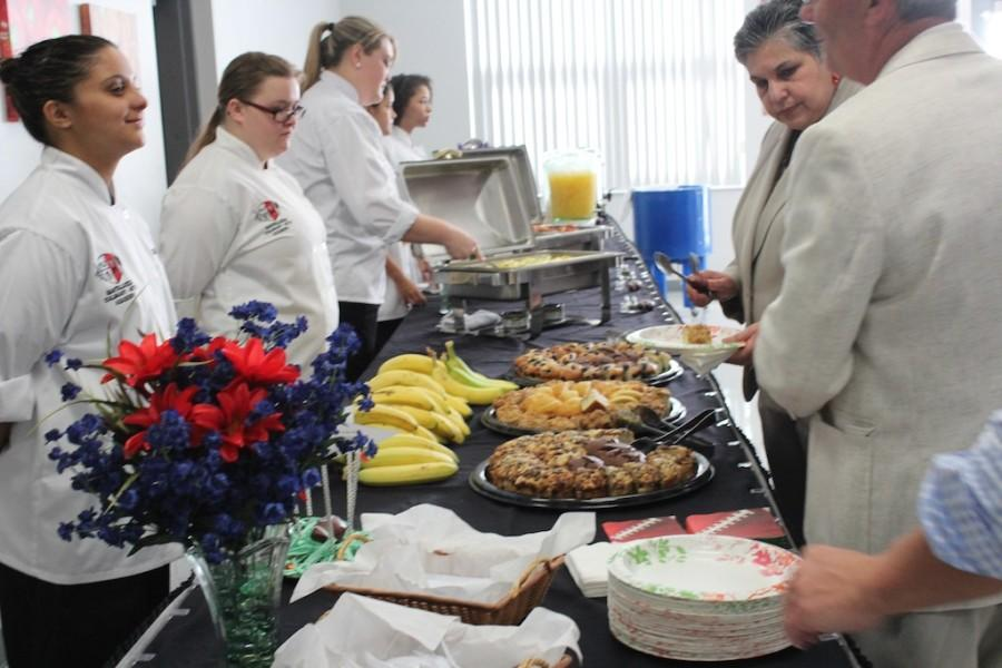 Culinary+Academy+students+Samantha+Veguilla%2C+Kimberly+Napier+and+Victoria+Hogue+serve+area+principals+at+a+meeting+in+the+Tomahawk+Cafe+hosted+by+Mrs.+Robinson.%0A
