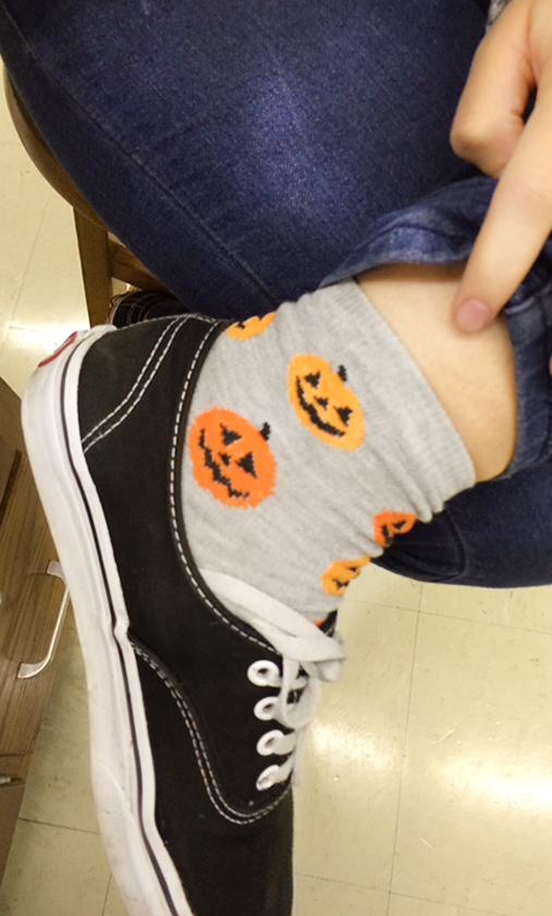 Baylee Johnson, a junior, sports a spooky pair of pumpkin socks in light of Halloween celebrations.