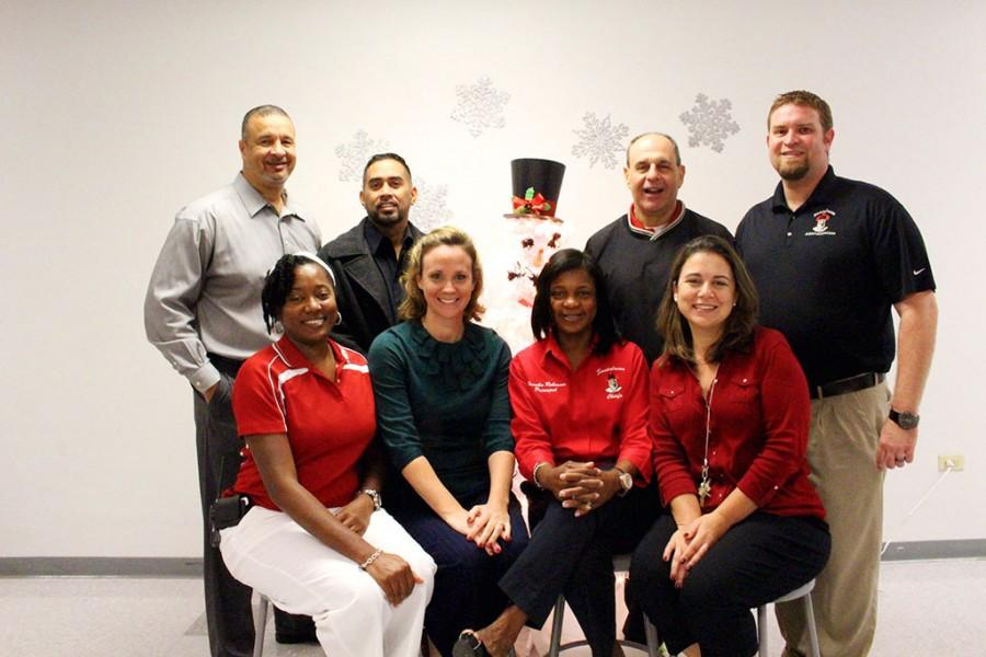 Mr. Gaddy, Mr. Ramos, Mr. Krupa, Mr. Montoya, Mrs. Mawali, Ms. Orndorff, Mrs. Robinson, and Mrs. Hayden all pose for a holiday picture during the Teacher Holiday Breakfast in the Tomahawk Cafe.
