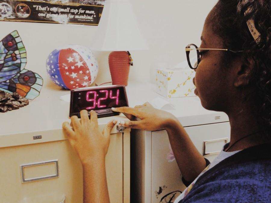 Johanne Damiscar adjusting the time in her classroom.