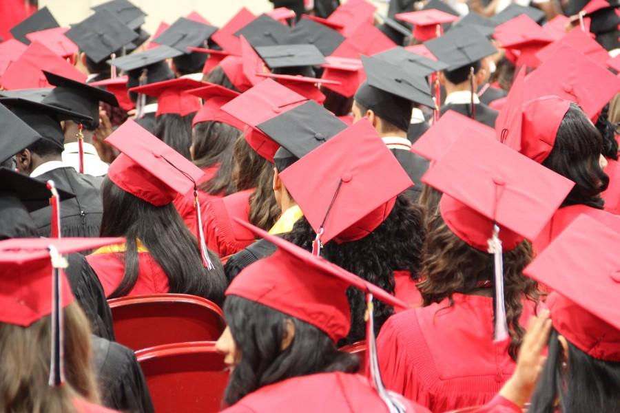 A sea of red and black caps waits for graduation to begin.