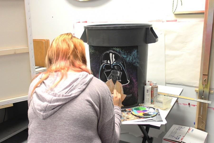 Senior+Nicole+Cohen+painting+a+garbage+can+for+Mr.+Badome.