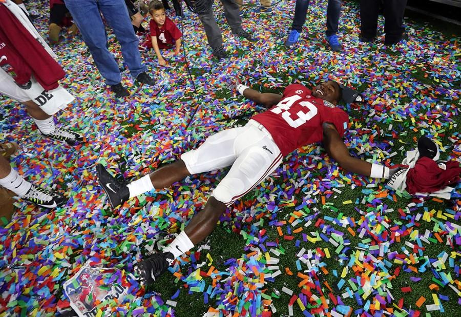 """Alabama running back Lawrence Erekosima (43) makes a """"confetti angel"""" after Alabama defeated Michigan State, 38-0, in the Goodyear Cotton Bowl at AT&T Stadium in Arlington, Texas, on Thursday, Dec. 31, 2015. (Richard W. Rodriguez/Fort Worth Star-Telegram/TNS)"""