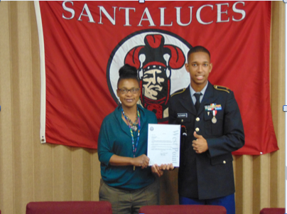 Mrs. Robinson and Dominic Alexandre in the principal's conference room accepting his scholarship.