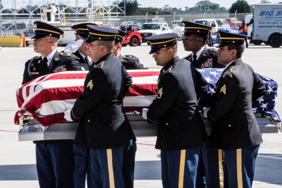 U.S. army remove the casket of Sgt. Sowell, draped in the American flag, from the Delta flight.