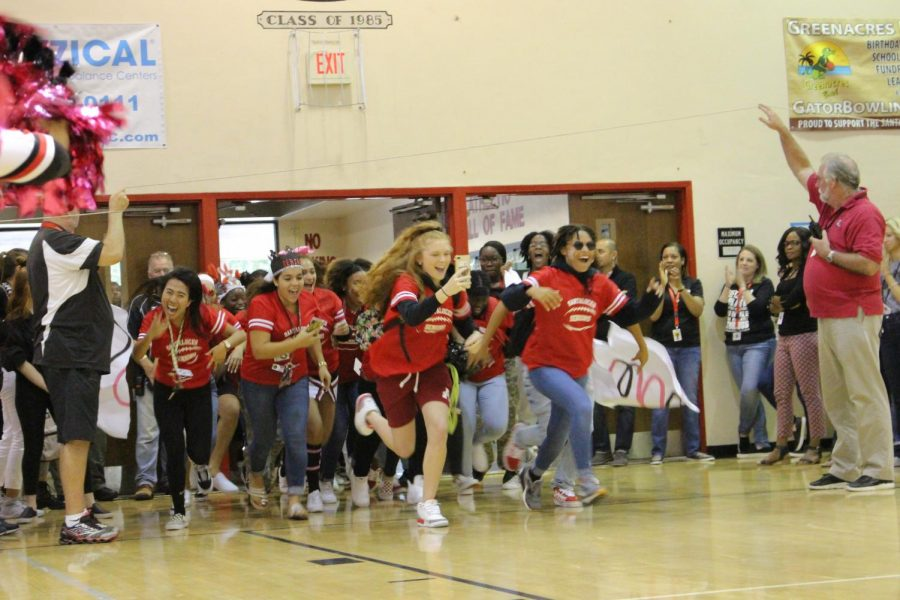 The senior powderpuff team runs into the gym during a pep rally