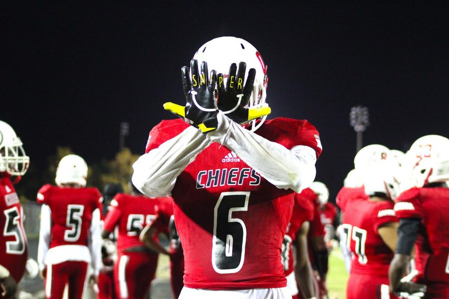 Santaluces football player Jerson Jacques (6) shows off his gloves before a regular season game against Olympic Heights.