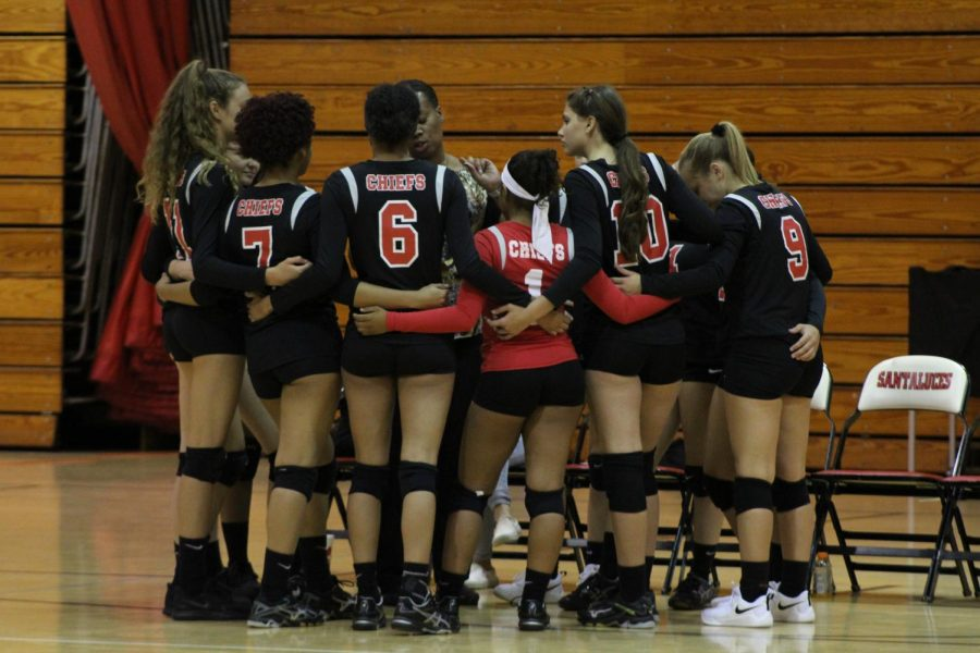 The entire varsity volleyball team in a huddle.
