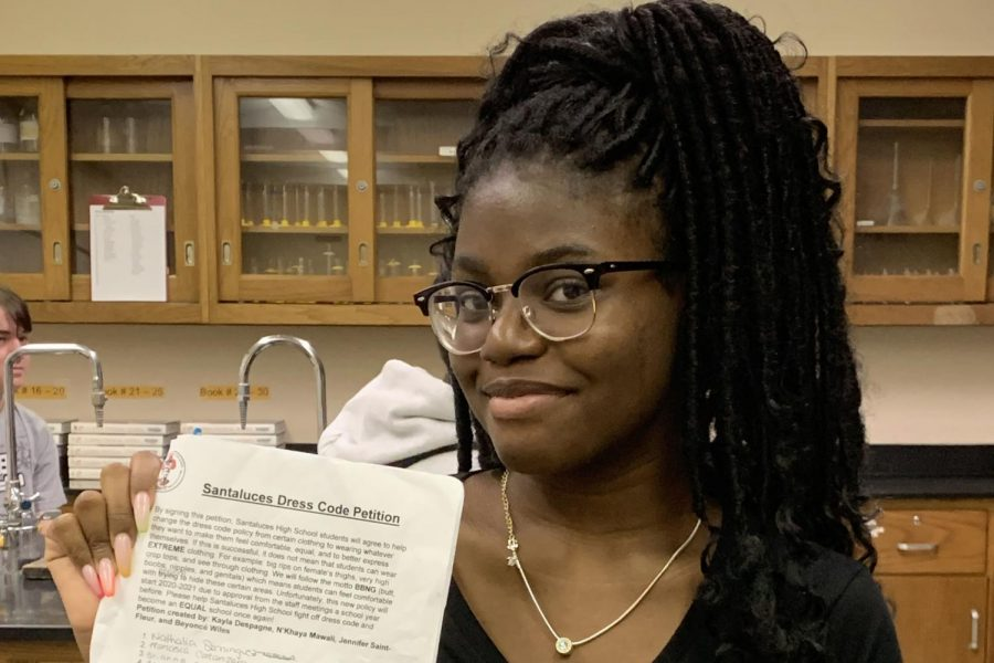 Junior Jennifer Saint Fleur holds the petition  she helped start to change the current dress code.