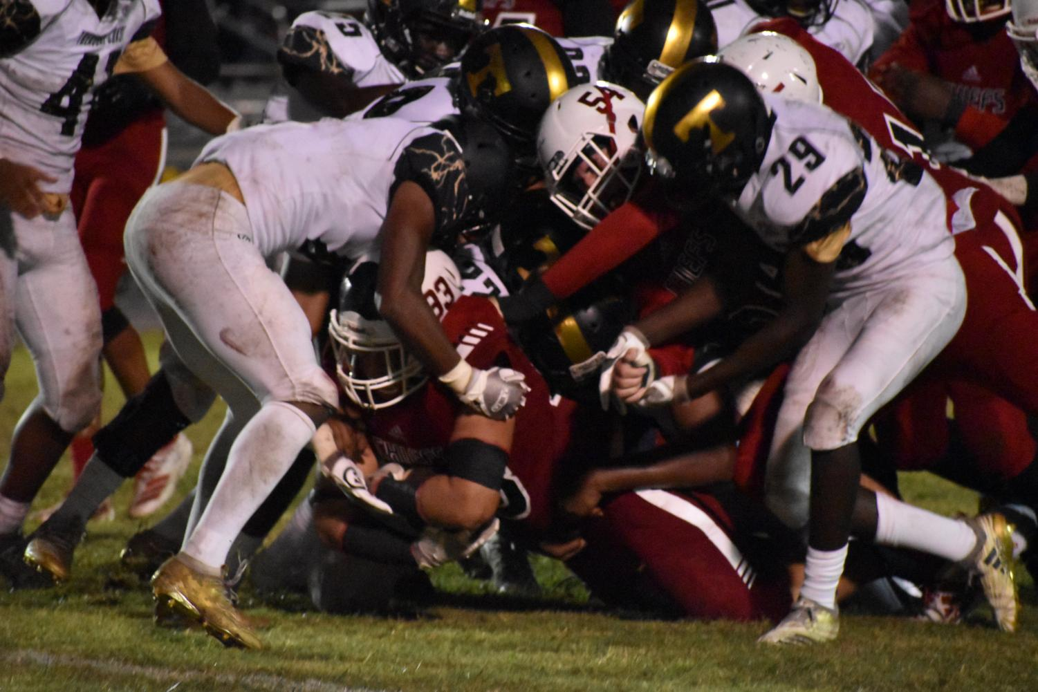 Coe Jr. grasps the ball as he gets covered in the Titan's defensive line.