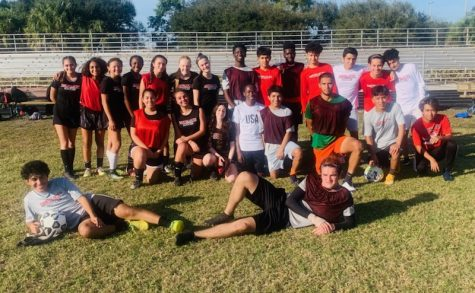 The boys and girls soccer teams coming together for a photo during practice.