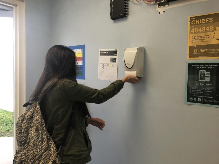 Student using the new hand sanitizer dispensers  before class.
