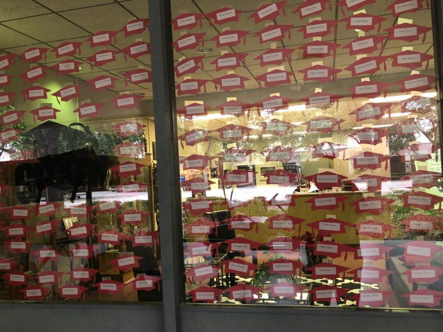 Graduation caps on the main office window.