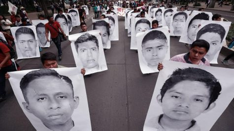 People holding up the faces of the missing.